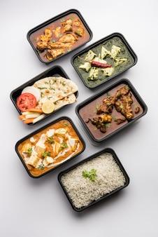 Cibo a domicilio online con paneer indiano al burro masala e palak paneer, montone e pollo al curry con roti e riso in contenitori di plastica