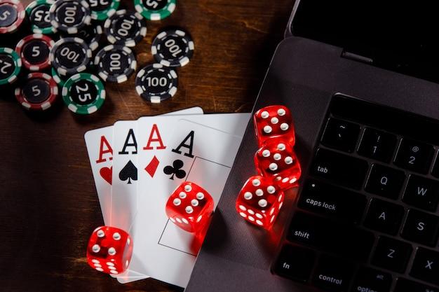 Concetto di gioco d'azzardo in linea rosso giocando a dadi chip e carte su una scrivania in legno vista dall'alto