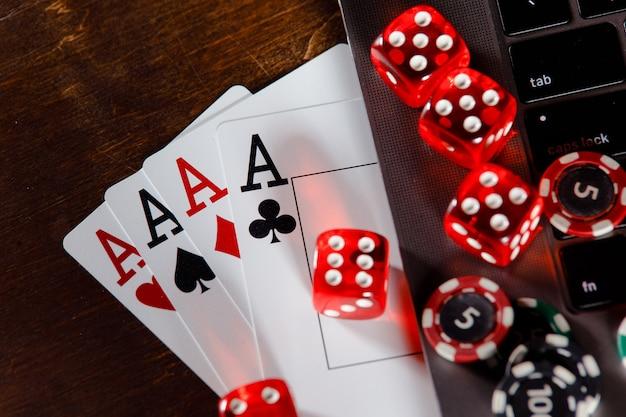 Concetto di gioco d'azzardo online rosso che gioca a dadi e carte su una scrivania in legno