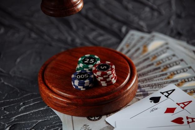 Gioco d'azzardo in linea e tema della giustizia, carte e martelletto del giudice sul vecchio tavolo grigio.