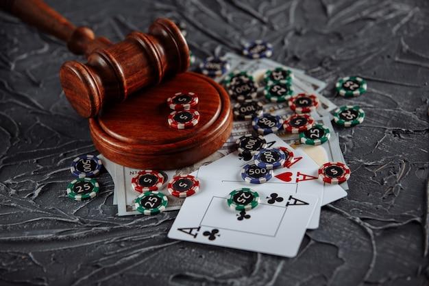 Gioco d'azzardo in linea e tema della giustizia, carte, gettoni da gioco e martelletto del giudice sul vecchio tavolo grigio.