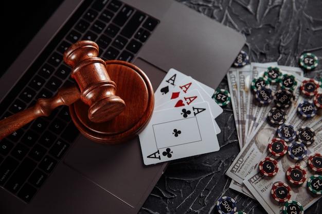 Gioco d'azzardo online e tema della giustizia, carte, chip di gioco e martelletto di legno del giudice sulla tastiera del laptop.