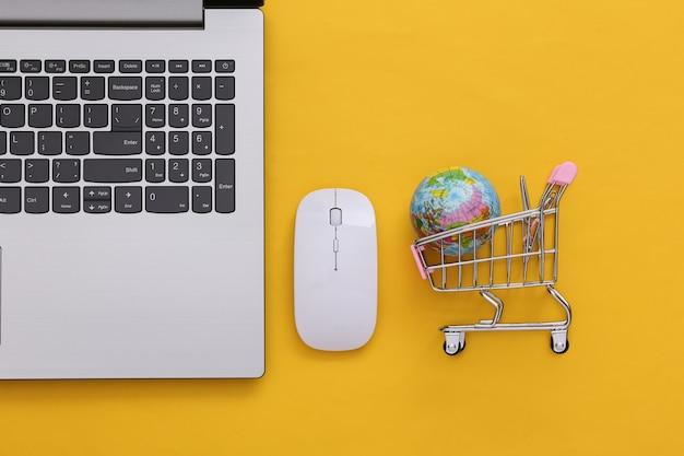 Supermercato online e globale. laptop e mini carrello della spesa con globo su sfondo giallo. vista dall'alto. lay piatto