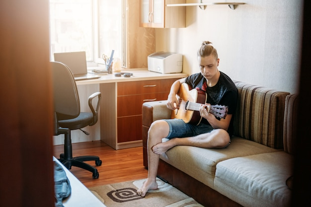 Lezioni di chitarra online adolescente caucasico che suona la chitarra con lezioni di chitarra online godendo