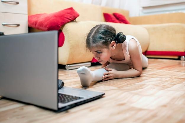 Hobby online, fitness, allenamento a distanza. giovane ballerina che pratica la coreografia classica e che fa la divisione della gamba durante la lezione di balletto in linea a casa prima del laptop, l'istruzione in linea