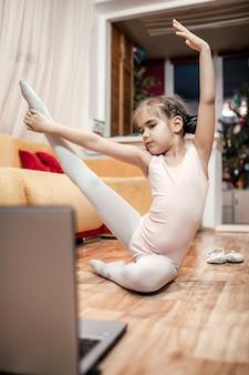 Hobby online, fitness, allenamento a distanza. giovane ballerina che pratica la coreografia classica durante la lezione di balletto in linea a casa prima del computer portatile, l'istruzione in linea