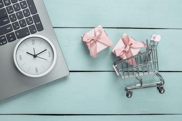 Online, shopping natalizio. carrello del supermercato con scatole regalo, laptop e orologio sulla superficie di legno blu. vista dall'alto