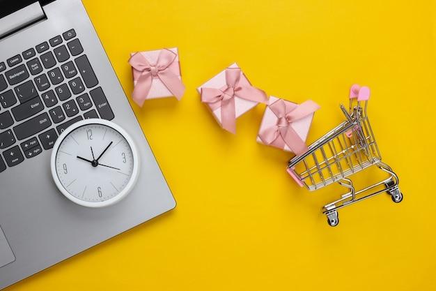 Online, shopping natalizio. carrello del supermercato con scatole regalo, laptop e orologio su una superficie gialla. vista dall'alto