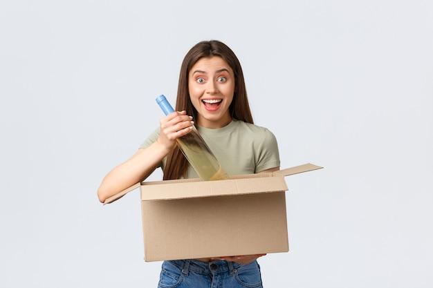 Consegna a domicilio online, ordini su internet e concetto di spesa. la donna eccitata ha ordinato la spesa in un negozio online, tenendo in mano una bottiglia di vino da asporto e sorridendo divertita.