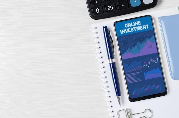 Investimento in linea. grafici e grafici sullo schermo dello smartphone. il concetto di investimento efficace di denaro. copia spazio.