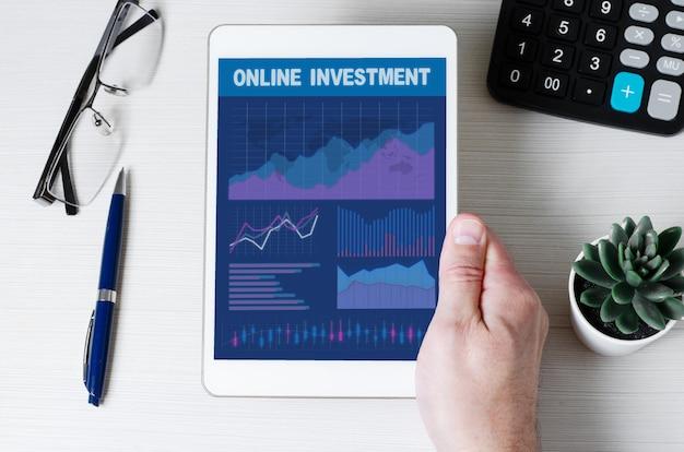 Investimento in linea. tablet con grafici e diagrammi nelle mani degli uomini.
