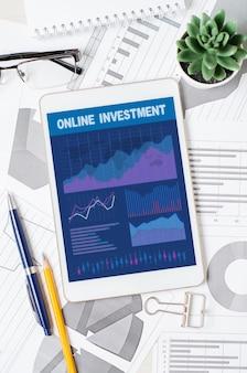 Investimento in linea. tablet con un'app mobile con grafici e tabelle. analisi dei processi aziendali o negoziazione in borsa.