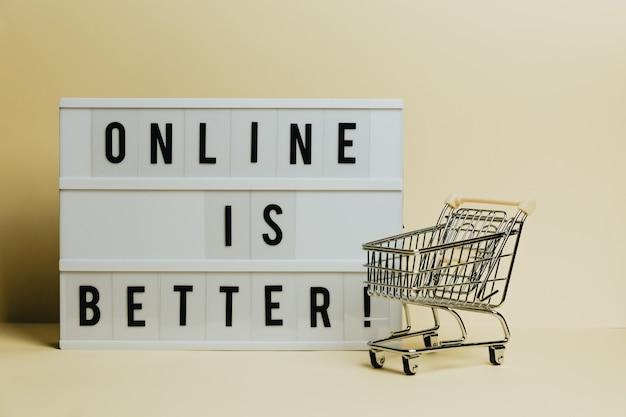 Online è il segno migliore, lo scatto commerciale, il concetto di e-commerce, il carrello del negozio con uno sfondo giallo pastello, lo spazio della copia e lo stile minimo
