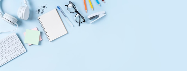 Concetto di design di apprendimento online. vista dall'alto del tavolo dello studente con computer, cuffie e articoli di cancelleria su sfondo blu del tavolo.