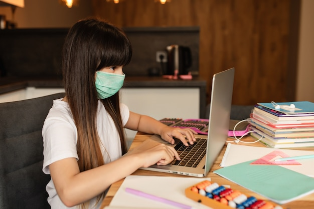 Apprendimento online durante la quarantena. la ragazza con una maschera protettiva sul viso fa i compiti a casa.