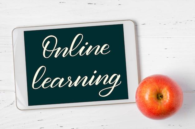 Apprendimento online - iscrizione scritta a mano su un tablet. il concetto di formazione a distanza per i bambini. compressa e mela su un fondo di legno bianco.