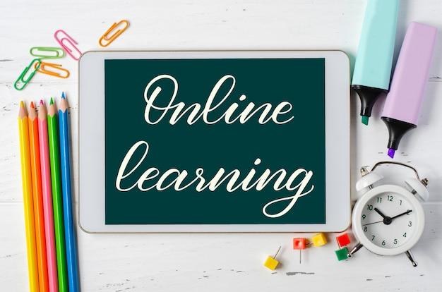 Apprendimento online - iscrizione scritta a mano su un tablet. il concetto di formazione a distanza per i bambini. tablet e forniture per ufficio su un fondo di legno bianco.