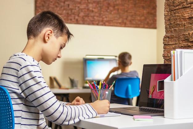 Apprendimento online, istruzione a distanza, apprendimento a distanza, entusiasmo. bambino che impara a casa
