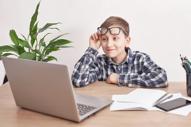 Lezione online a casa, distanza sociale durante la quarantena, autoisolamento, concetto di istruzione online, scuola a casa. ragazzo che impara la lingua online, usando il computer portatile, istruzione a distanza. studente, scuola