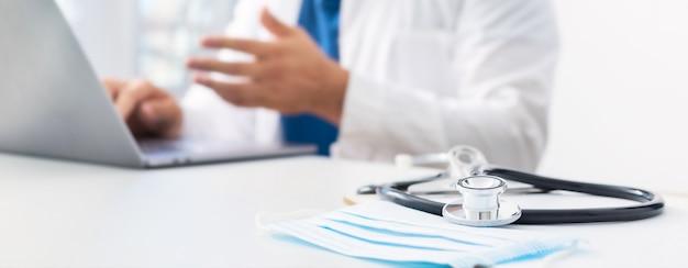 Concetto di medicina online. stetoscopio e mascherina medica sul posto di lavoro dei medici in background. medico conduce una consultazione paziente in linea utilizzando il laptop