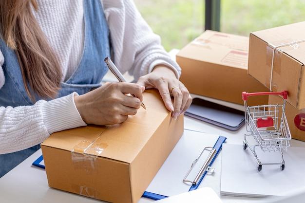 I commercianti online scrivono le informazioni sulla spedizione dei clienti sulla parte anteriore della cassetta dei pacchi, imballano la merce in una cassetta dei pacchi e la inviano tramite una società di trasporti privata. concetto di acquisto online