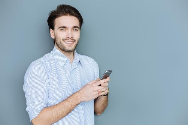 Messaggistica in linea. bel giovane positivo ti guarda e sorride mentre digita un messaggio sul suo smartphone