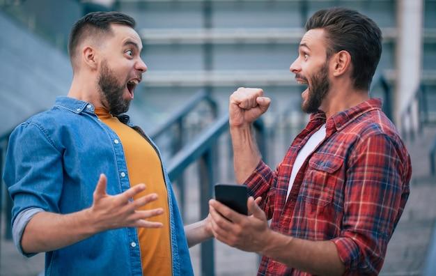 Denaro e scommessa online. i migliori amici eccitati felici moderni con lo smart phone stanno gridando e tengono i pugni in alto per vincere qualche partita