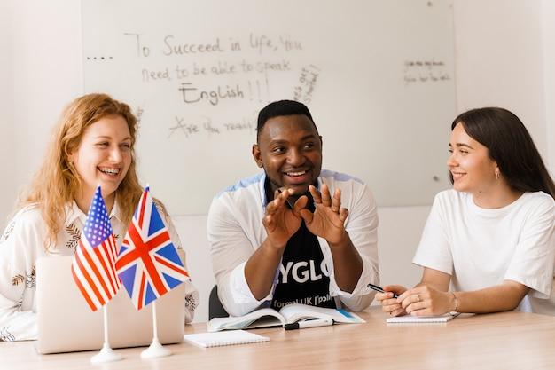 Un attraente gruppo multietnico online di insegnanti studia e ride, discute qualcosa