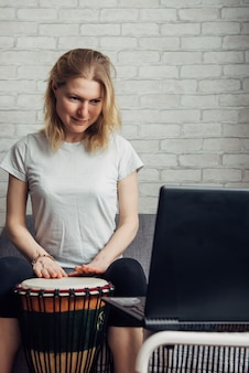 Lezioni di musica online. insegnamento a distanza per suonare il tamburo. la giovane donna guarda il video corso sul gioco del djembe. hobby e attività ricreative in blocco