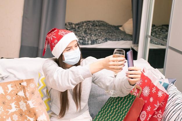 Online capodanno e auguri di natale. una ragazza con cappello e maschera da babbo natale chiama la famiglia e gli amici tramite collegamento video con un bicchiere di champagne