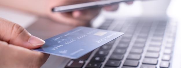 Acquisto a pagamento online, pagamento elettronico con carta di credito, concetto di smart phone, laptop su sfondo bianco tavolo con carrello carrello, primo piano.