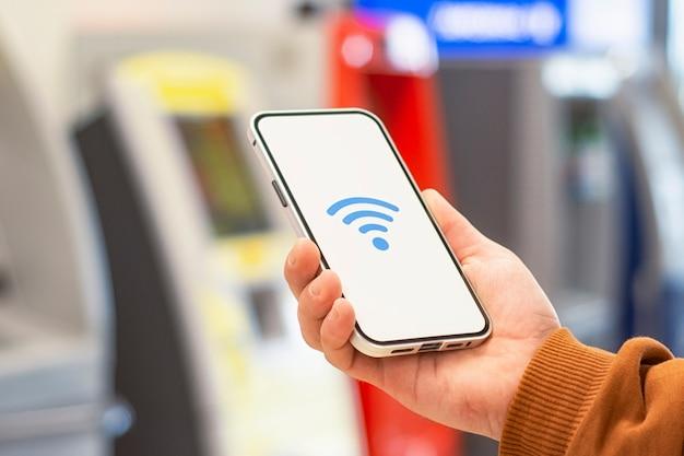 Pagamenti on line. display del telefono con icona wi-fi sullo sfondo di un bancomat. l'uomo tiene uno smartphone nel suo primo piano della mano.