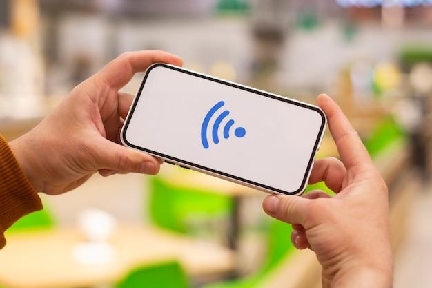Pagamenti on line. display del telefono con icona wi-fi sullo sfondo di un ristorante. l'uomo tiene in mano uno smartphone in primo piano