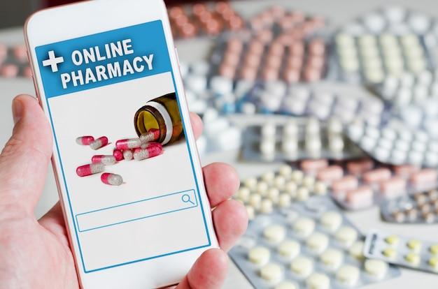 Farmacia online. applicazione nel tuo smartphone per l'ordinazione online di medicinali. telefono in primo piano della mano dell'uomo. molte pillole.