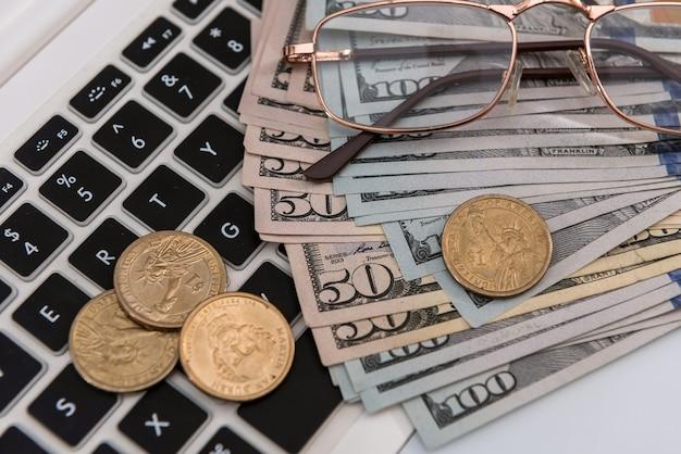 Computer portatile di vendita online e dollaro con gli occhiali, concetto di risparmio