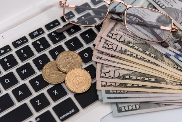 Vendita online laptop e dollaro con occhiali, concetto di risparmio