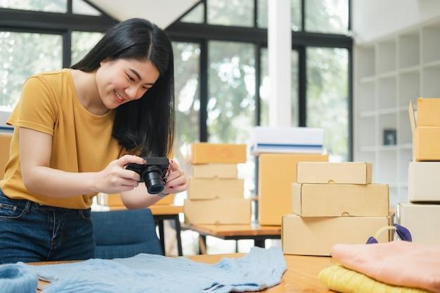 Il proprietario del venditore online scatta una foto del prodotto per caricarla nel negozio online del sito web. vendita online, shopping online e concetto di e-commerce.