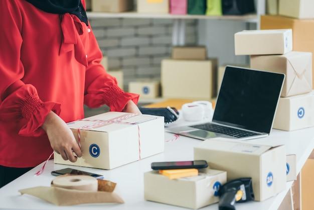 Il venditore online lavora a casa e confeziona la scatola di consegna al cliente.