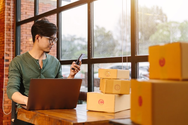 I giovani asiatici dello shopping online iniziano una piccola impresa in una scatola di cartone al lavoro. il venditore prepara la scatola di consegna per il cliente, per le vendite online o per l'e-commerce.