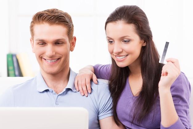 Acquisti online. bella giovane coppia di innamorati che fa shopping online mentre si siede sul divano insieme