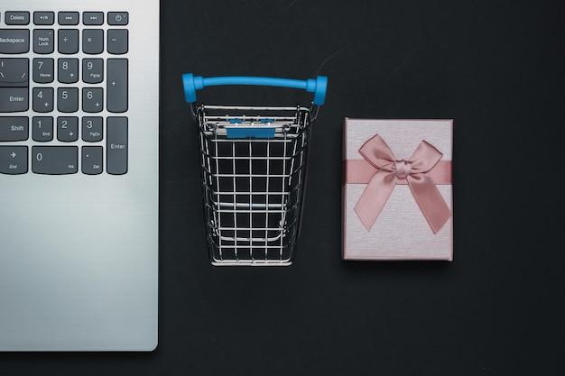 Shopping online, composizione venerdì nero. laptop, scatole regalo con fiocchi, carrello della spesa su sfondo nero.