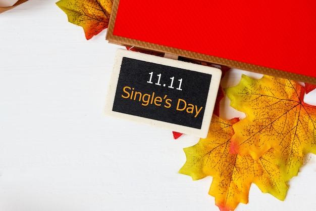 Acquisto in linea della cina, concetto di vendita di giorno del singolo 11.11. mini lavagna per testo e foglia d'acero con vendita di testo 11.11 single's day su sfondo bianco.