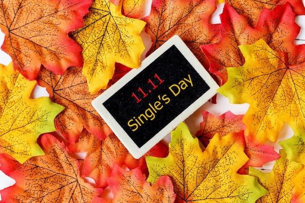 Acquisto in linea della cina, concetto di vendita di giorno del singolo 11.11. mini lavagna per testo e foglia d'acero con testo vendita 11.11 single's day su superficie bianca.