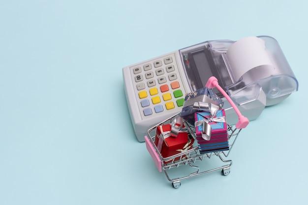 Concetto di acquisto online. primo piano di un registratore di cassa accanto a un carrello con scatole di regali avvolte su sfondo blu, vista dall'alto, spazio di copia. concetto di affari