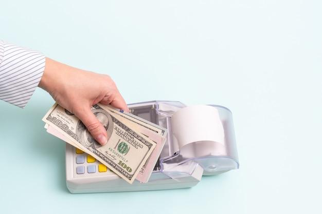 Concetto di acquisto online. primo piano di una mano femminile che tiene diverse centinaia di banconote in dollari sopra il registratore di cassa per pagare un prodotto o un servizio su sfondo blu, vista dall'alto, spazio di copia.