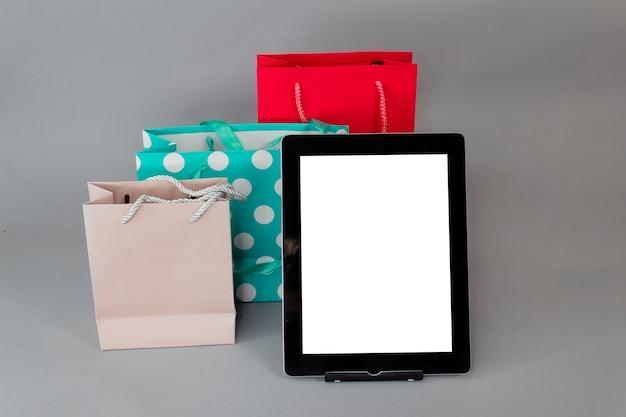 Concetto di acquisto online. mockup di tablet close-up con schermo bianco con sacchetti regalo luminosi su sfondo grigio.