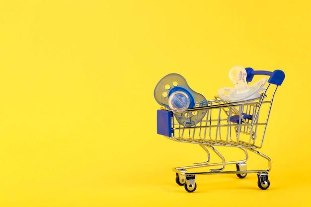 Concetto di acquisto online. e-commerce, prodotti per l'infanzia, ciuccio. sfondo giallo. copia spazio.