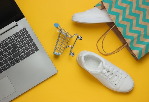 Concetto di shopping online colpo di studio di moda scarpe da ginnastica bianche del computer portatile nel carrello della spesa del sacchetto di carta