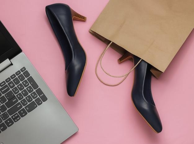 Concetto di shopping in linea colpo dello studio di moda scarpe a tacco alto delle donne del computer portatile in sacchetto di carta