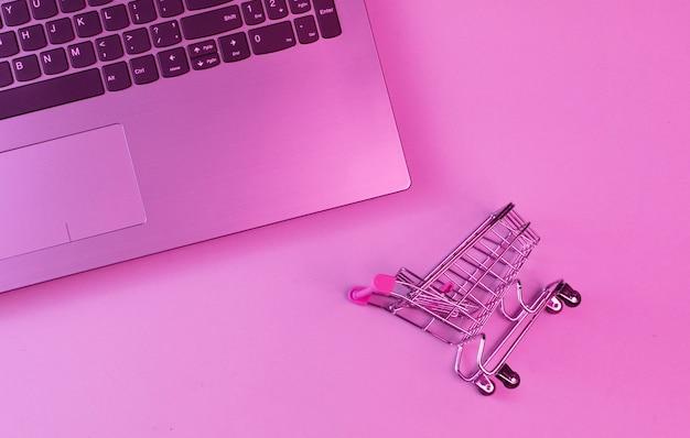 Concetto di acquisto online. carrello della spesa per laptop